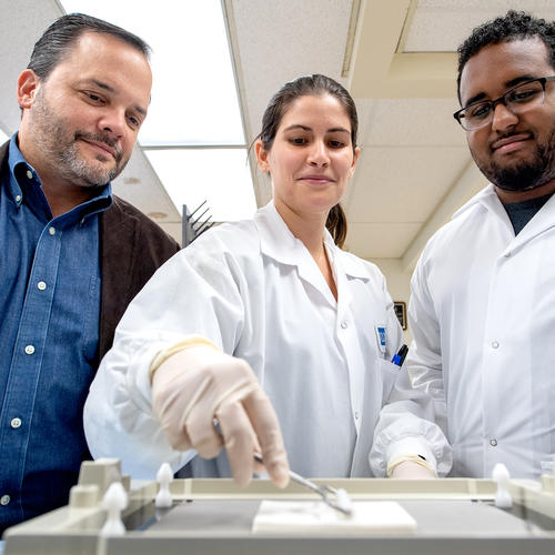 (L-R) Dr. Luis Montaner oversees an experiment conducted by members of his lab